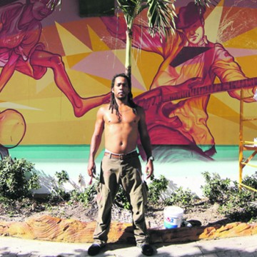 PHOTO COURTESY OF peter vahan COLORFUL IMAGINATION:  Ruben Gerado Ubiera Gonzalez stands before his mural at 1925 Harrison St. painted as part of the Downtown Hollywood Mural Project.